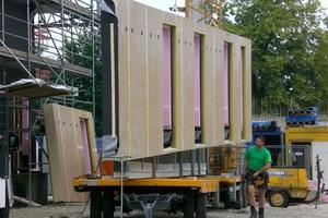 """<div class=""""bildtext"""">Sämtliche Holztafelelemente wurden vorproduziert. Per Tieflader kamen die Elemente zur Montage direkt auf die Baustelle, so dass sie sofort montiert werden konnten.</div>"""