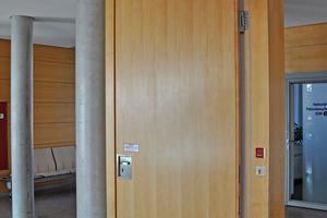 """<div class=""""bildtext"""">Brandschutztür mit Feststellanlage: Signalgeber sind ein externer Rauchmelder (links oben) und ein manueller Türschließer (roter Taster rechts im Bild). </div>"""