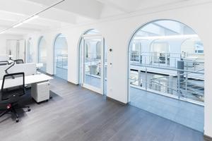 """<div class=""""bildtext"""">Die Glastüren und die Systemverglasung gewähren den Büromitarbeitern einen guten Blick ins Atrium. Dabei ist dieses akustisch, thermisch und brandschutztechnisch von den Arbeitsplätzen abgetrennt. </div>"""