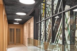 """<div class=""""bildtext"""">In den Bereichen, in denen Brücken als Teil der umlaufenden Flure der Verglasung vorgelagert sind, sorgen LEDs für eine gleichmäßige Ausleuchtung des Mosaiks.</div>"""