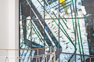 """<div class=""""bildtext"""">Das Mosaik wurde auf eine Brandschutzverglasung auflaminiert und die montagefertigen Scheiben in eine Pfosten-Riegelfassade aus dem Stahlprofilsystem """"VISS Fire"""" montiert.</div>"""
