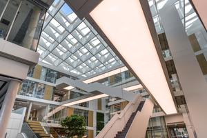 """<div class=""""bildtext"""">Den Kern des Gebäudes bildet das zentrale mehrgeschossige, glasüberdeckte Atrium mit Treppen und Stegen, über die die Obergeschosse erschlossen werden.</div>"""
