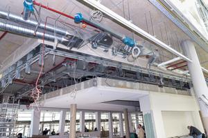 """<div class=""""bildtext"""">Zugang vom Atrium zur Kantine: Im Deckenbereich musste ein automatischer Brandschutzvorhang in die Unterkonstruktion integriert werden.</div>"""